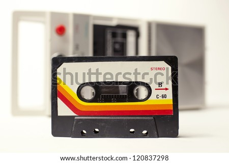 an old audio cassette in front of a retro tape player - stock photo