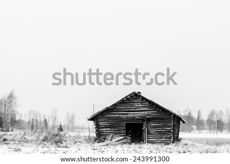 An old barn house covered in snow in the rural Finland. - stock photo