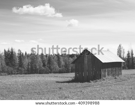 An old barn in the countryside. Image taken in a sunny day in Finland. Image in black and white. - stock photo
