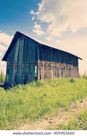 An old barn in the green field in Finland. Image taken on a sunny day and some clouds are in the sky. Image has a vintage effect applied. - stock photo