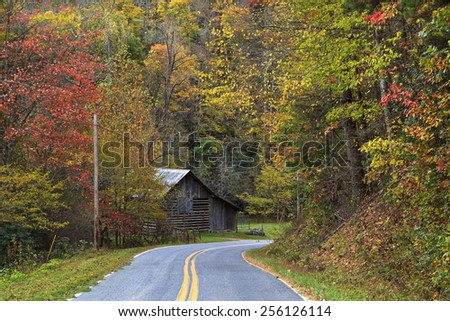 An old barn sits beside a country road in the fall. - stock photo