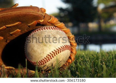 An old baseball glove laying on the grass. - stock photo