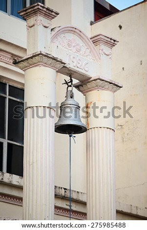 An old bell hanging at a historical archway dated back 1926 at Buddhist Maha Vihara Temple. - stock photo