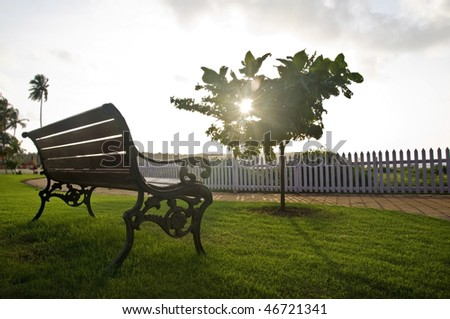 An old bench in the park at against sunset. - stock photo