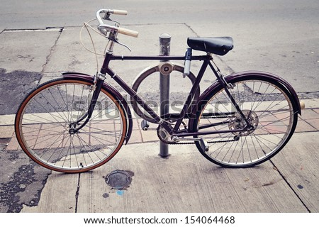 An old bicycle locked up on the street in Toronto - stock photo
