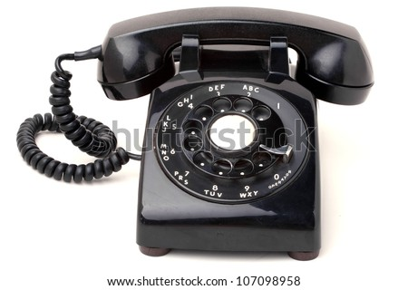 An old black antique rotary style telephone isolated over a white background.