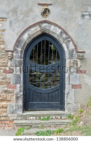 An Old Black Arched Door - stock photo