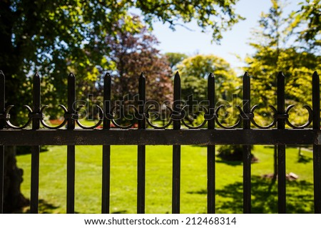 An old black, wrought iron fence around a formal garden - stock photo