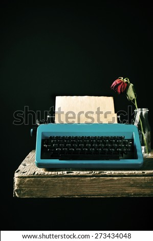 an old blue typewriter with a bank page in its roller and a wilted red rose in a glass vase on a rustic wooden table, against a black background - stock photo