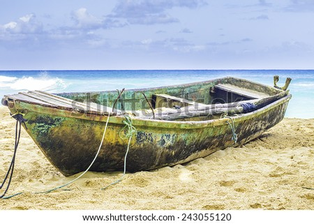An old boat laying on beach sand with bright blue water in the background. - stock photo