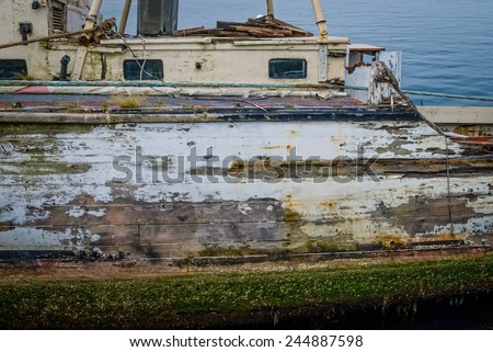 An old boat with peeling paint, algae and barnacles. - stock photo