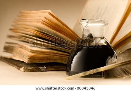 An old book with a feather and the inkpot full of ink