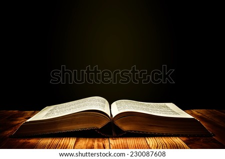 An old book with magical yellow aura around it. - stock photo