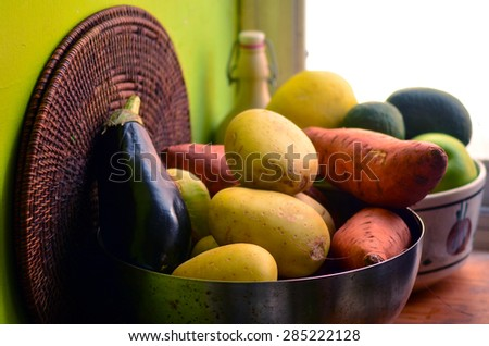 An old bowls with fresh vegetables and fruits in the kitchen - stock photo