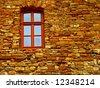 An old brick wall with a red window. - stock photo
