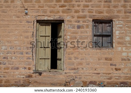 An old brick wall with a very very weathered wooded door and window. - stock photo