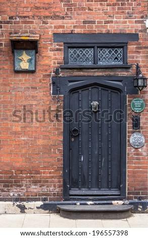 An old brick wall with black wooden door seen in Rye, Kent, UK - stock photo