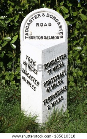 An old British road milestone showing distances to York and Tadcaster, Ferrybridge, Pontefract and Doncaster. - stock photo