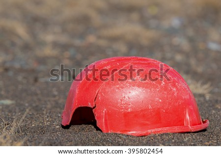 An old, broken hardhat lying on the ground. The hardhat is a faded and scratched red, and has a piece missing from it. It is also cracked. There is room for text above. - stock photo