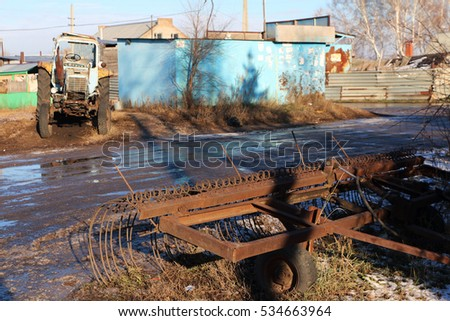 An old broken rusted tractor in the Russian village against a blue sky