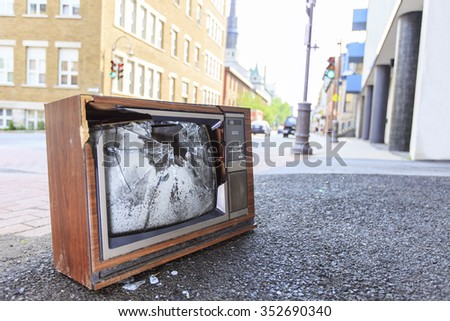 An old broken TV left on the street. - stock photo