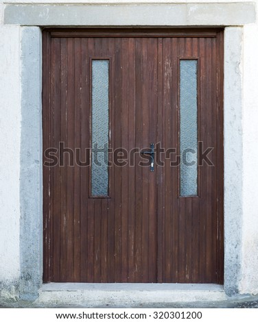 an old brown ragged shabby wooden door - stock photo