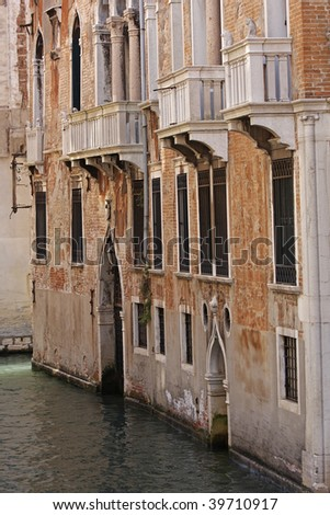 An old building facade fronts onto a canal in Venice