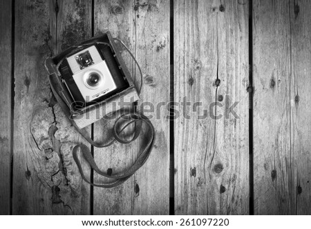 An old camera in its original vintage leather case on a wooden background in black and white - stock photo