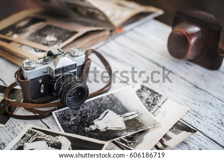 An old camera with black-and-white photos and vintage album on a wooden table. Vintage background.
