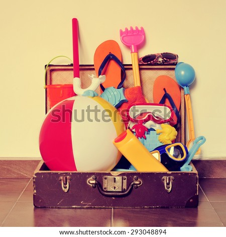 an old cardboard suitcase full of beach items, such as diving masks, pails and shovels, a beach ball, sunblock or flip-flops, placed on the floor, with a retro effect - stock photo