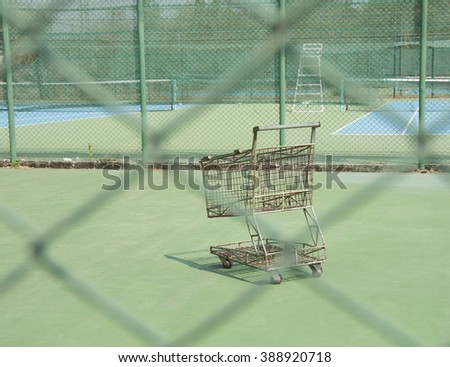 An old cart in tennis court with Chain fence.