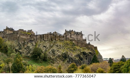 An Old castle on a hill with a dramatic cloud filled sky