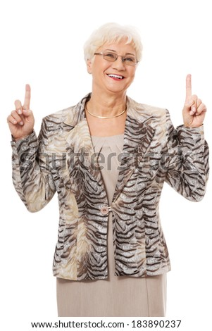 An old casual lady pointing up on copy space. Isolated on white.