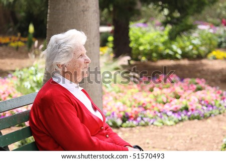 an old caucasian octogenarian sitting on a park bench relaxing in the sun - stock photo