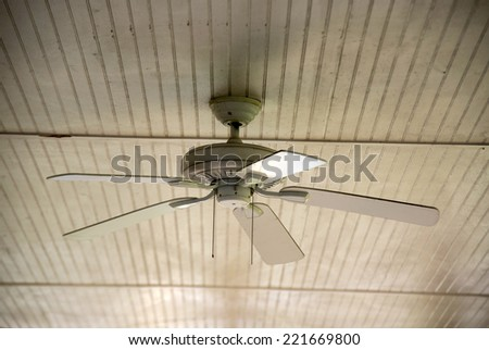 An old ceiling fan against a wooden siding - stock photo