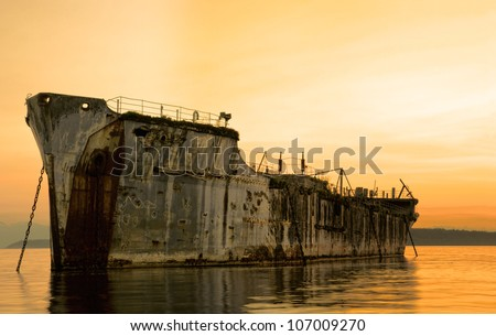 An old cement freighter moored as a breakwater for a log pond.