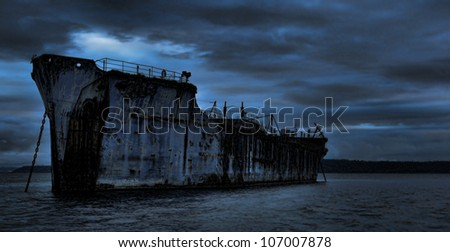 An old cement freighter rests peacefully as a breakwater for a log pond. - stock photo