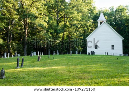 An old cemetery sits behind a historic country church. - stock photo