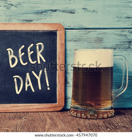 an old chalkboard with the text beer day written in it and a jar with refreshing beer on a rustic wooden table, against a blue wooden background - stock photo