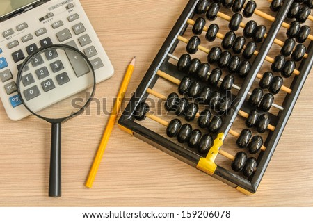 An old chinese abacus and modern calculator and pencil and glass