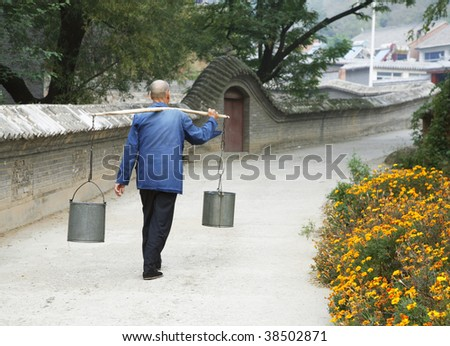 An old Chinese man is carring waters on his way back home. - stock photo