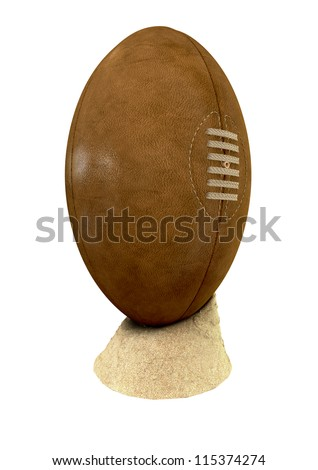 An old classic leather rugby ball with laces and stitching placed on a small pile of beach sand on an isolated background - stock photo