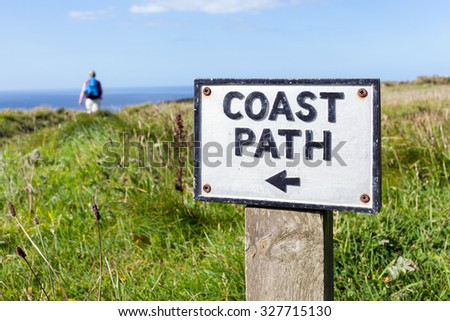 An old coast path sign on the Cornish cliffs near Tintagel, UK.  Selective focus on the sign with a female walker out of focus in the background