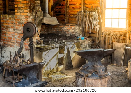 An old colonial Blacksmith shop at sunrise as the sunlight flows through a window - stock photo