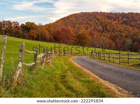 An old country road lined with a split rail fence turns as the autumn leaves glow with color against the North Carolina sky. - stock photo