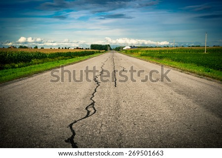 An old cracked, damaged and repaired country asphalt road stretches ahead toward its vanishing point on the distant horizon with corn fields on either side.