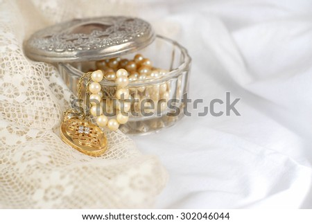 An old crystal jewelry box with the aged silver lid off contains strands or pearls and a gold and diamond locket. All items are on soft cotton and delicate lace fabric in white and ivory. Copy space.  - stock photo