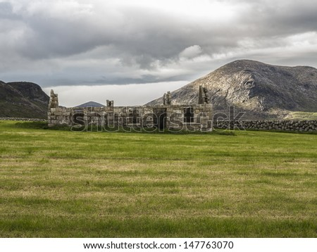 an old derelict house with slieve binnian in the mournes of ireland behind it - stock photo