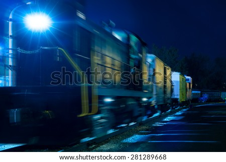 An old diesel locomotive and freight cars glow in an eerie blue under the night lights of a rail yard