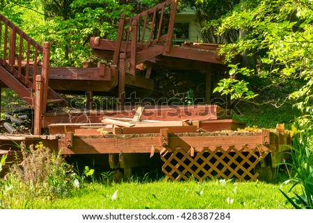 An old, dilapidated backyard deck in the process of being dismantled and removed - stock photo